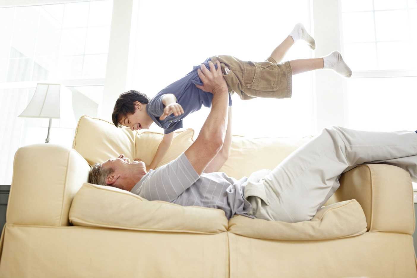 A father playfully throwing his son up into the air while lying on a sofa
