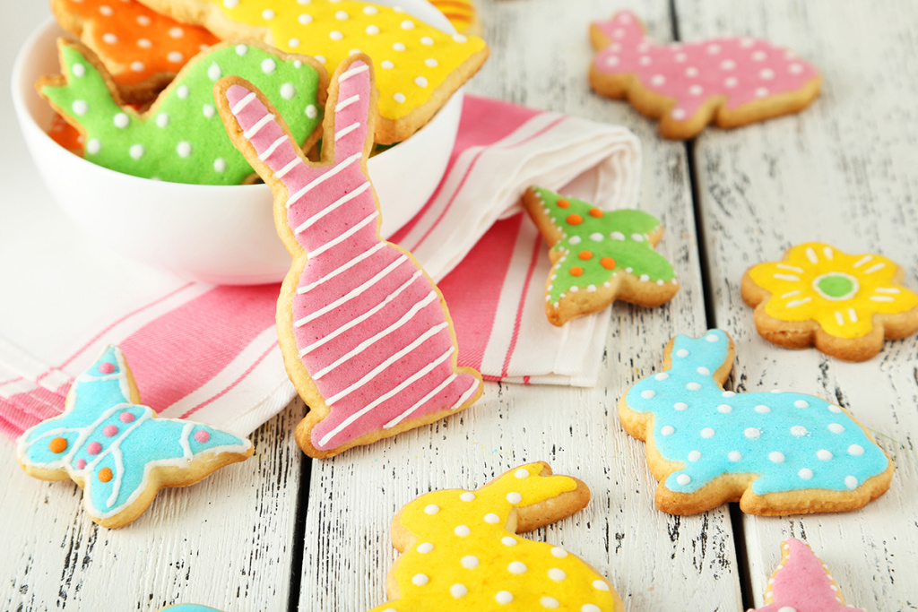 Colorful easter cookies on white wooden background