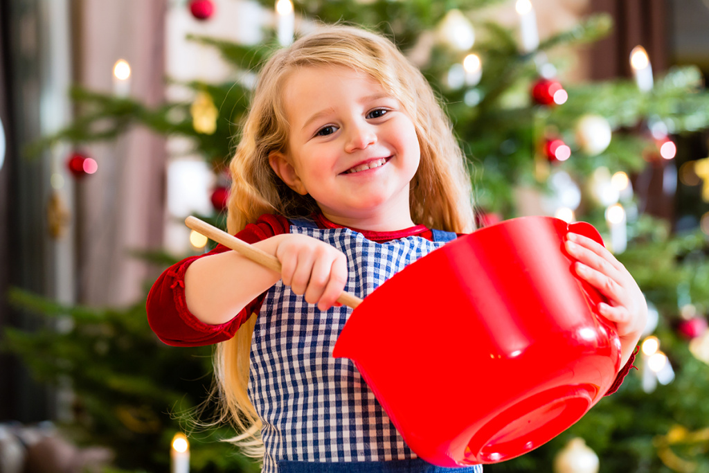 Child baking X-mas cookies at home in domestic kitchen with Christmas tree